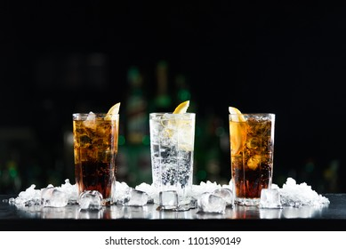Two whisky and coke cocktails and one white alcoholic drink on the bar table.