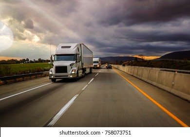 Two white 18 wheelers on highway platooning