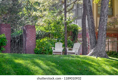 Two white adirondack chairs setting under tall trees on a shady hill in front of ornate iron garden fence and two story Tudor style home
