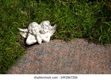 Two white angels on a marble plate
