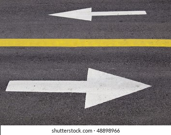 Two white arrows painted on a roadway, separated by a solid yellow line, each indicating the required direction