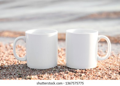 Two white black mugs in the sand near the sea