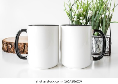 Two white blank 15oz coffee mugs side by side with black rims and handles on white background with flower decor, coffee mug mockup