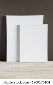 Two white blank canvases of different sizes stand against a dark wall. Mockup. Materials for painting with oil paints and acrylics. Close-up photo.