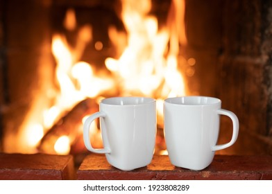 Two white blank mugs for mockup in fireplace decorations. Mugs with hot tea standing on fireplace. Cozy and romantic winter day. Close up mugs with copy space.