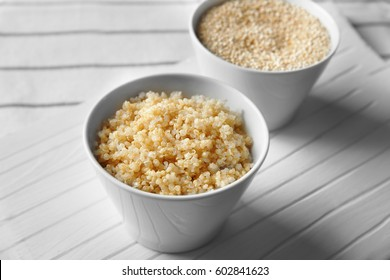 Two white bowls with sprouted organic quinoa grains on white wooden board