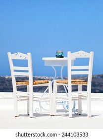 Two white chairs and a blurred panoramic view of the hills of santorini, Greece.