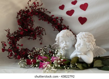 two white cherubs with red and pink roses with a grapevine heart shaped wreath.