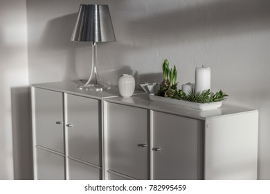 Two white chests in a bright room with a stylish decor. On top of the chest of drawers there are a candle stand, a lamp and a composition of candles and plants.