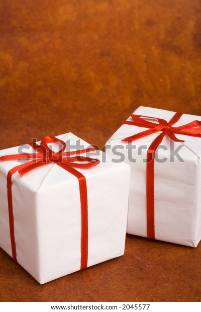 Two white Christmas or birthday gift boxes with red ribbon