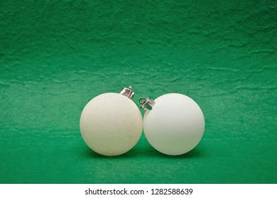 Two white Christmas tree baubles on a green background