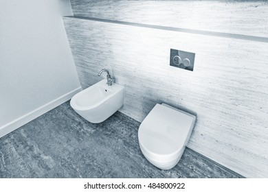 Two white closed toilet bowls in the bathroom.