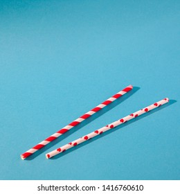 Two white cocktail straws with red stripes and hearts on a blue background