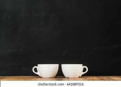 two white coffee cups arranged together on wood texture surface show clean and simple design ideas drawing area on black chalkboard wall background.