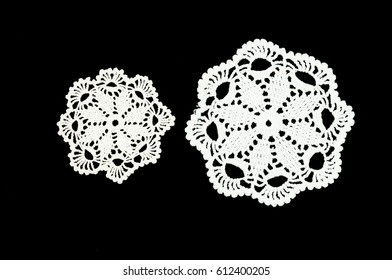 Two white crocheted coasters lace doily on the black background