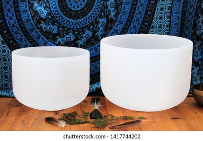 Two white crystal singing bowl on a wooden floor with an altar and a blue Indian type of linen decoration in the background