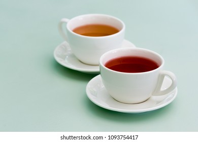 Two white cup of herbal tea on the mint table. Feels cozy.