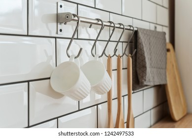 Two white cups, cutlery on hook and dishes in the white modern kitchen, organizing space