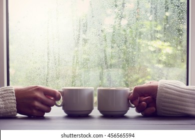 two white cups in hands on a background of wet window with raindrops / comfortable coffee break for two people