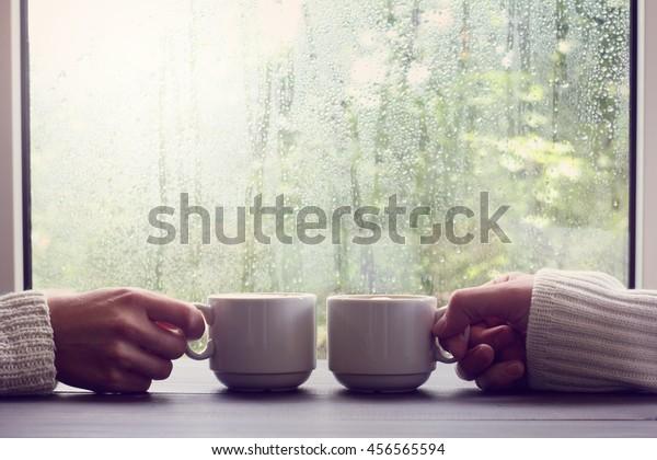 雨のしずくの窓の背景に2つの白いカップ/2人用の快適なコーヒー休憩