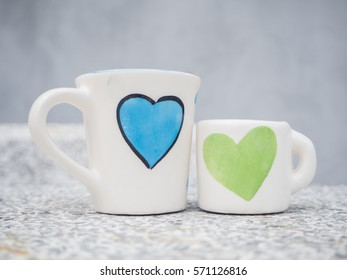two white cups and size on marble table with blue and green heart printed