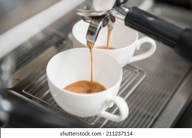 Two white cups standing on the grating of coffee machine and coffee pouring into them