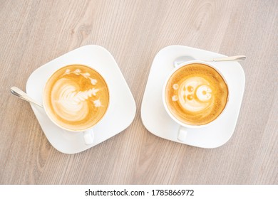 Two white cups of tasty cappucino. Top view. Romantic meeting concept. Wood texture table background.