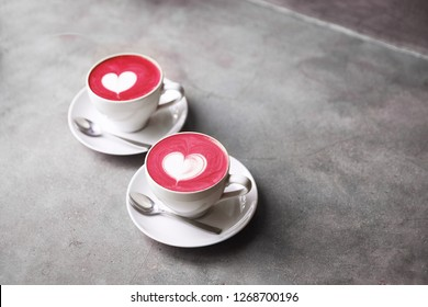 Two white cups of trendy corolful beetroot latte with love art latte. Valentine's concept. Concrete grey backdrop.