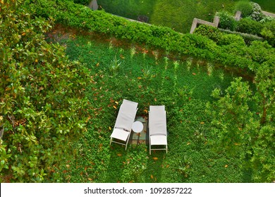 Two white deckchairs on the lawn of a house; top view.