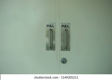 Two white doors with metallic pull sign and door knob in metallic style.