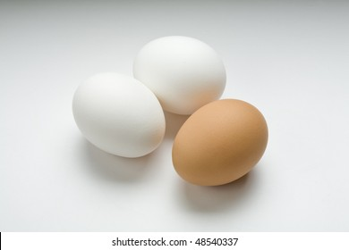 Two white eggs and one brown egg on white