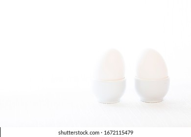 Two white eggs in white porcelain stands. The background is white. A close-up photo in a high key.