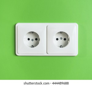 Two white electrical power sockets on a green wall