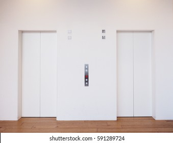 Two white elevators in building.