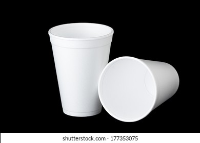 Two white empty styrofoam cups on black background. One stands upright and the second cup lays next to the first.