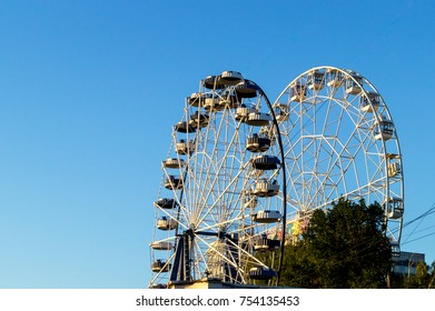 Two the white ferris wheels with the clear blue sky at Russia