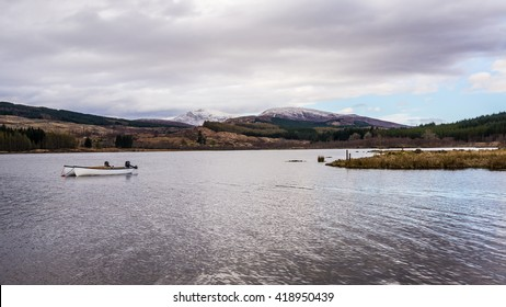 Two white fishing boats with outboard engines on a placid Scottish loch with snow covered mountains in the background
