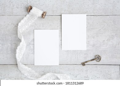 Two white greeting cards mockup on a white wooden desk. Blank, closed card template with white ribbon, spool and antique key. Flat lay.