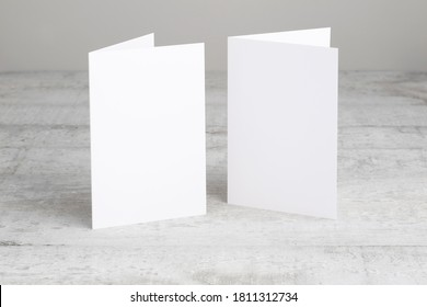 Two white greeting cards mockup, standing upright on a white wooden desk. Blank, closed cards template.  - Shutterstock ID 1811312734