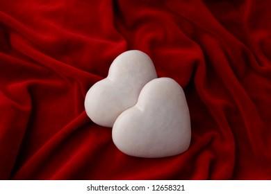 two white honey-cakes heart over purple velvet