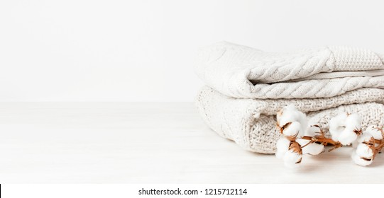 Two white knitted woolen sweaters pullover in a stack and branch of cotton on wooden table on light background. Fashion Clothes Trendy Cozy Jumper Autumn Winter look Delicate cotton flowers