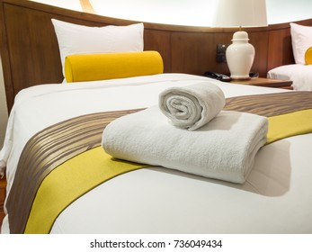 Two white laundered fluffy towels on white bed in bedroom interior at the hotel