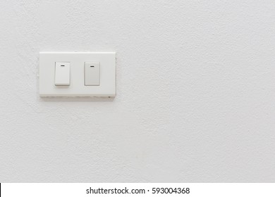 two white lighting switchs on concrete wall, on and off