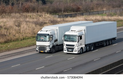 Two white lorries driving side to side on the motorway