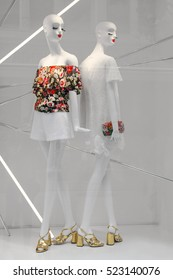 Two white mannequins standing in a modern store window