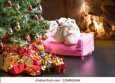 Two white mice and a grey mouse sitting on a pink sofa next to the Christmas tree and a fire burning in the fireplace behind them