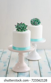 Two white mini wedding cakes covererd with fondant with gum paste succulents on cake stands