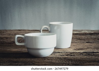 two white mug on wooden tabletop against grunge wall. vintage tone