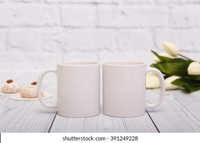 Two white mugs with cookies and flowers behind them