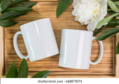 Two white mugs, cups wedding mockup. Peony, green leaves, wooden background. Summer gifts, boho style